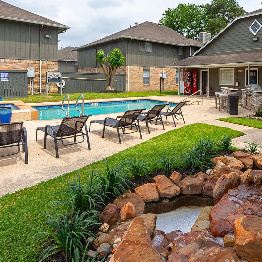 rock water feature next to outdoor swimming pool and jacuzzi